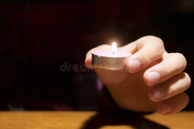 Fine sulle mani che tengono una candela nello scuro sopra la superficie di legno f fotografie stock libere da diritti
