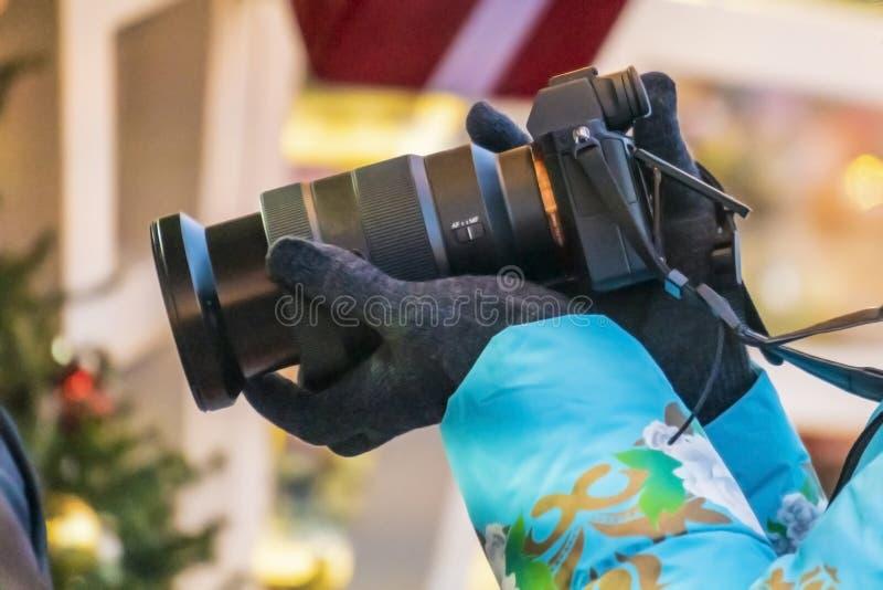 Fine sulle mani femminili che tengono un photocamera e sparare video nella via f fotografia stock libera da diritti