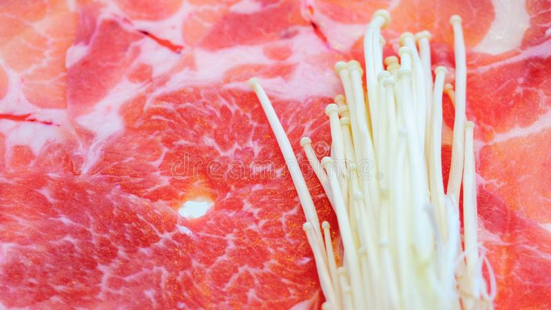 Fine sullo scorrevole marmorizzato crudo fresco della carne di maiale e sul fungo dorato dell'ago o sul fungo di enoki impilato s fotografia stock