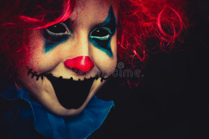 Fine terrificante del pagliaccio sul ritratto di Halloween su fondo nero fotografia stock