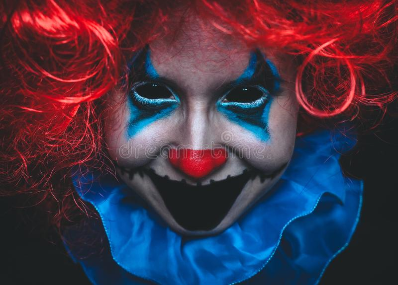 Fine terrificante del pagliaccio sul ritratto di Halloween su fondo nero fotografia stock libera da diritti