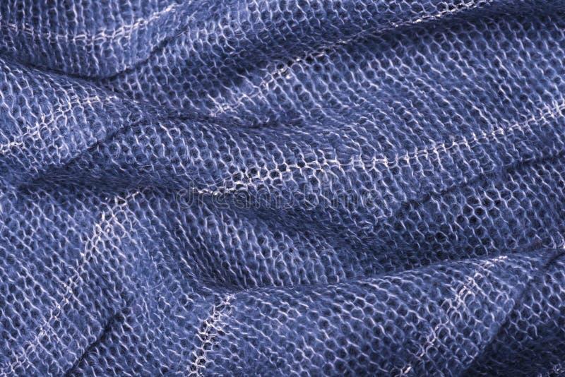 Fine tricottata blu di struttura del tessuto su Può essere usato come fondo Fuoco selettivo immagini stock libere da diritti