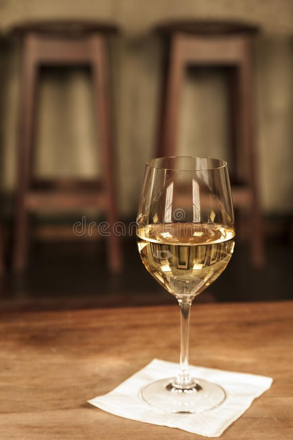 Fine white wine Chardonnay in crystal wineglass on table in upscale bar restaurant bistro with barstools in background. stock photo