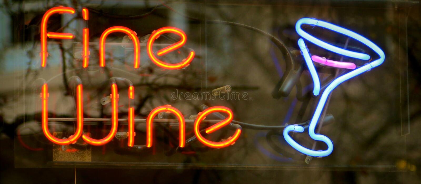 Wine Neon Sign. An orange and blue neon sign displays fine wine in a store window stock photo