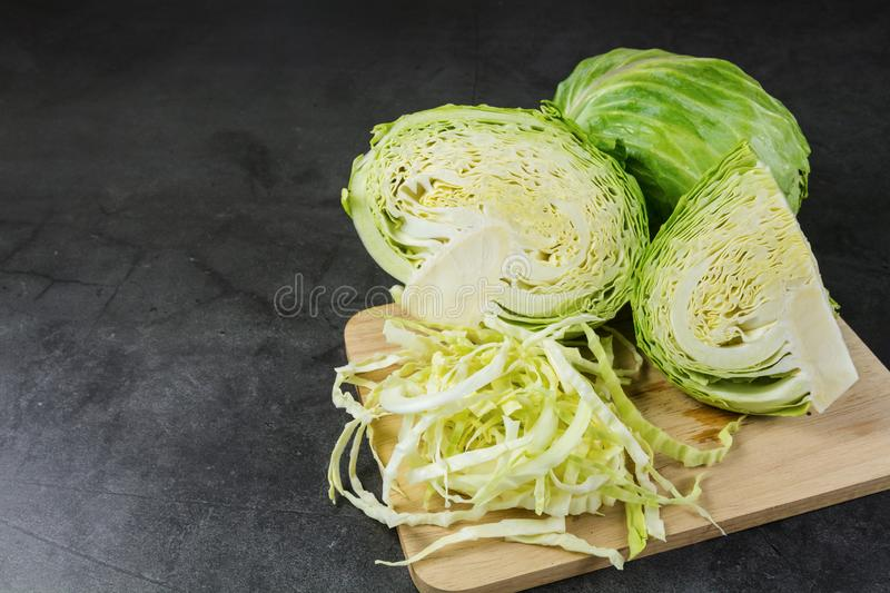 Finely chopped cabbage on a chopping board And cauliflower on black ground royalty free stock photography