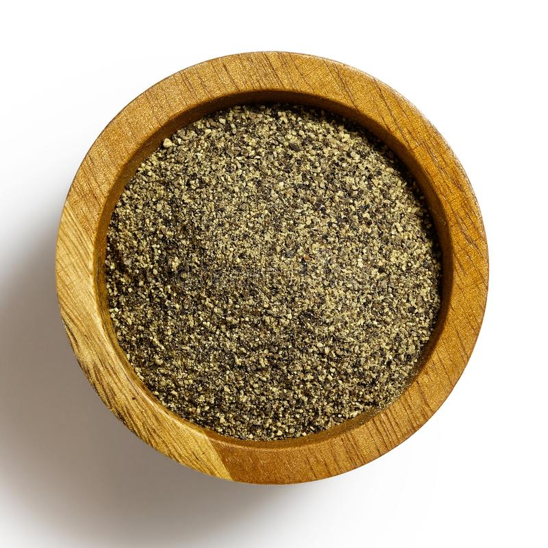 Finely ground black pepper in dark wood bowl isolated on white. royalty free stock image