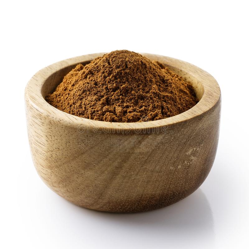Finely ground cinnamon in dark wood bowl. royalty free stock images