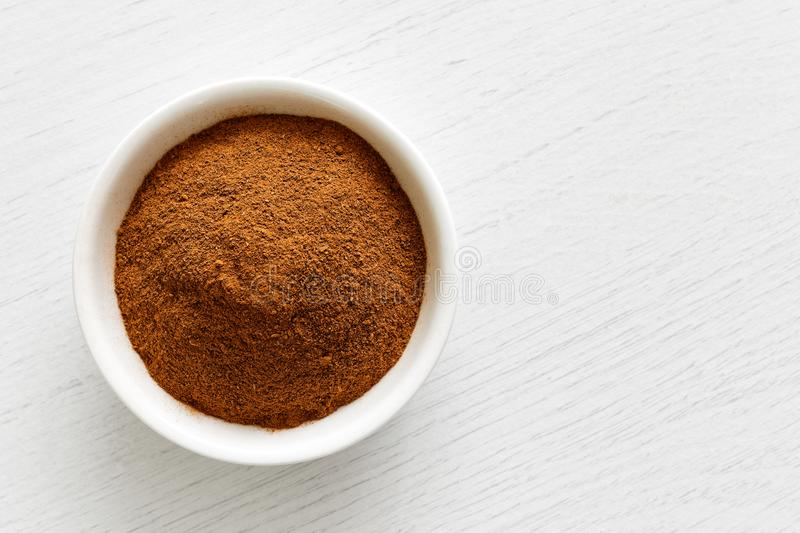 Finely ground cinnamon in white ceramic bowl isolated on white w. Ood background stock photo