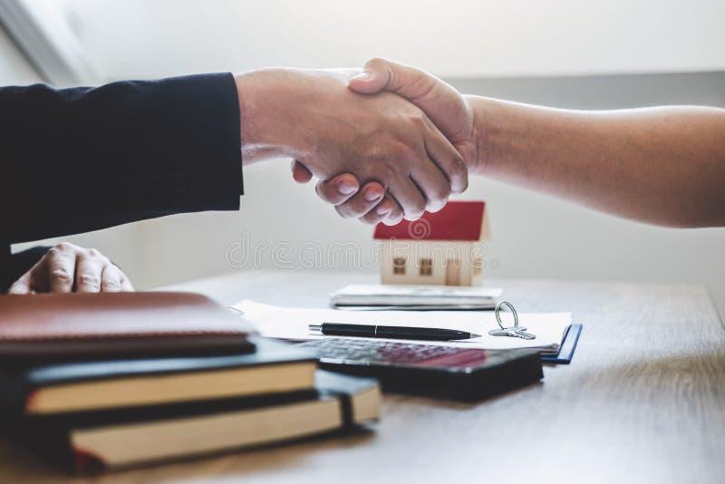 Finendo al riuscito affare del bene immobile, del mediatore e del cliente stringere le mani dopo la firma del modulo di domanda a fotografie stock