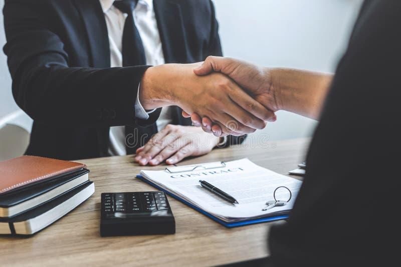 Finendo al riuscito affare del bene immobile, del mediatore e del cliente stringere le mani dopo la firma del modulo di domanda a immagine stock libera da diritti