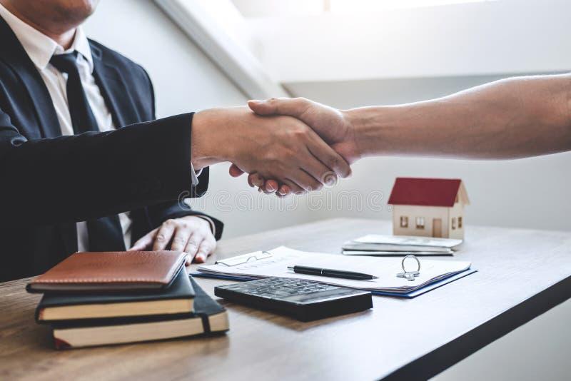 Finendo al riuscito affare del bene immobile, del mediatore e del cliente stringere le mani dopo la firma del modulo di domanda a fotografia stock