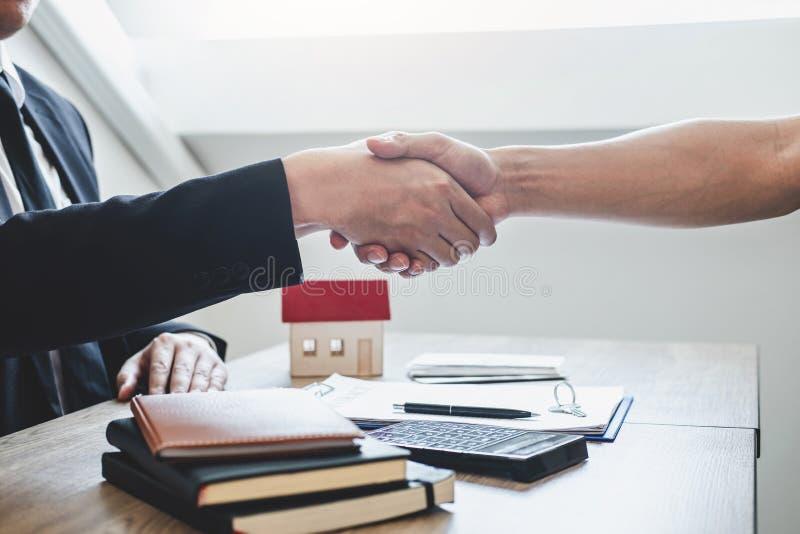 Finendo al riuscito affare del bene immobile, del mediatore e del cliente stringere le mani dopo la firma del modulo di domanda a fotografia stock libera da diritti