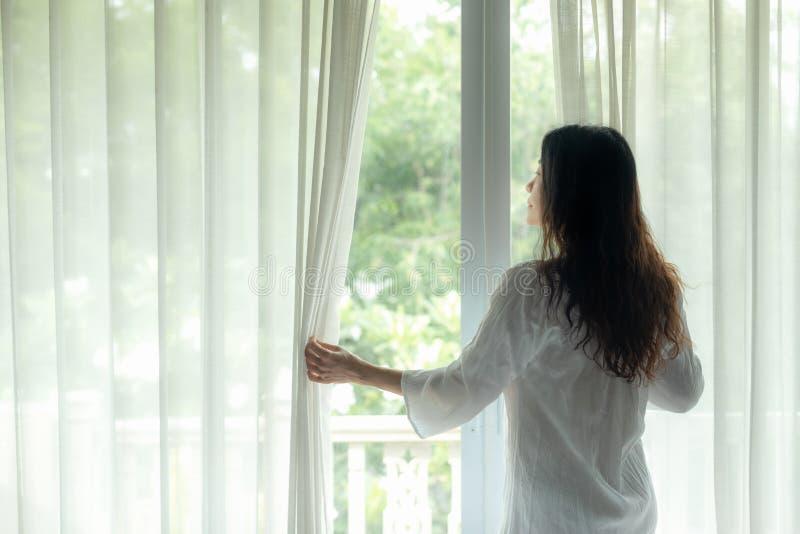 Finestra aperta delle donne di stile di vita dopo alzarsi il letto bianco nell'alba di mattina per rilassarsi umore immagini stock