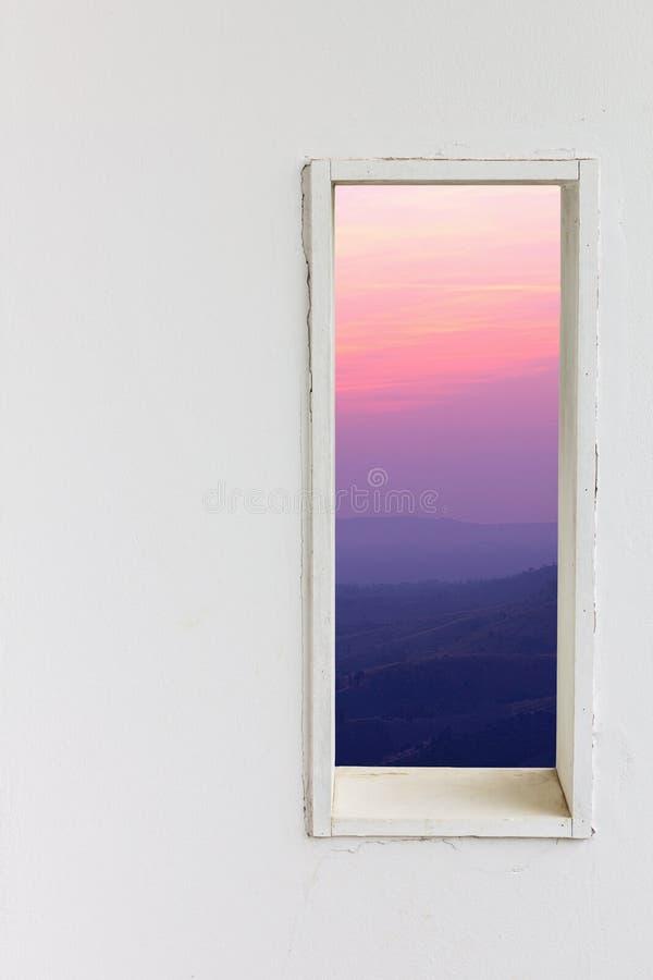 Finestra bianca della parete con il Mountain View di tramonto immagini stock
