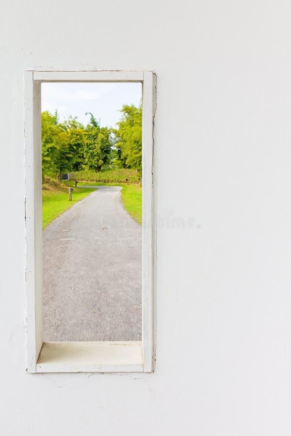 Finestra bianca della parete con il passaggio pedonale nella vista del giardino fotografia stock libera da diritti