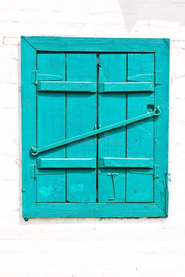 Finestra con gli otturatori blu verniciati di legno chiusi immagine stock libera da diritti