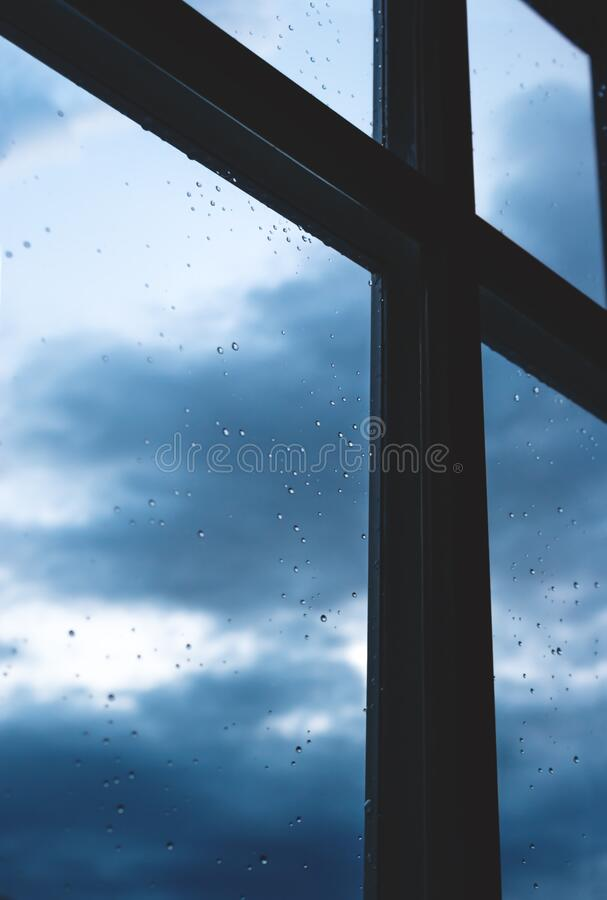 Finestra con goccioline pioggia con vista sul paesaggio blu scuro immagini stock libere da diritti