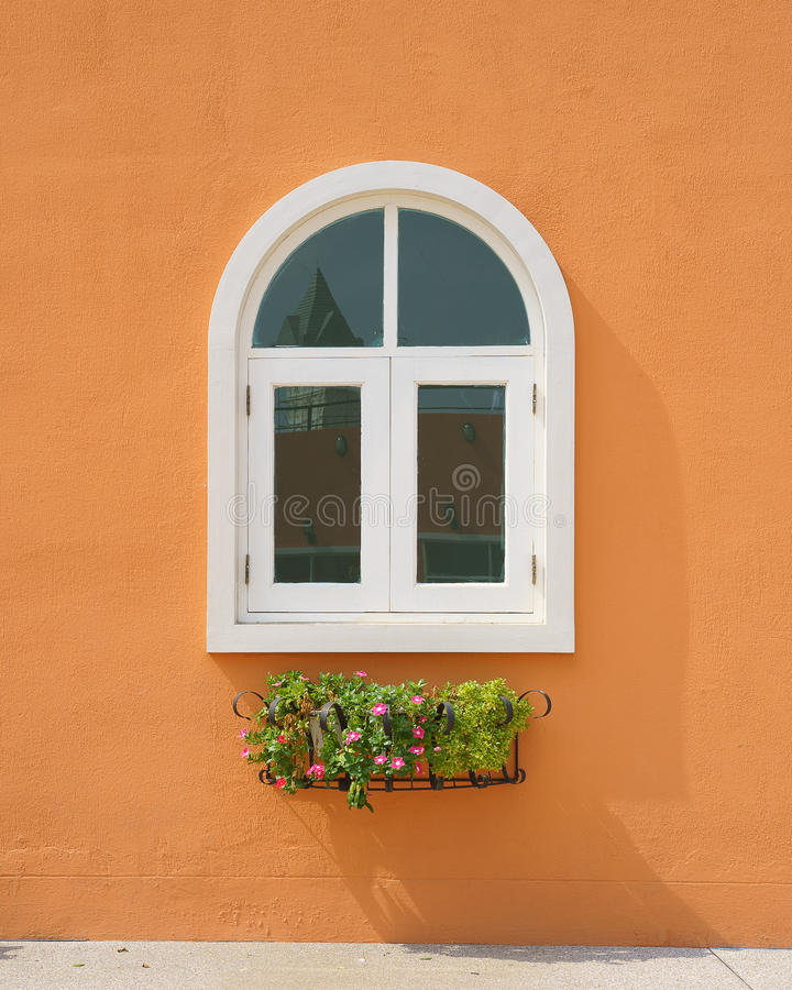 Finestra d'annata sulla parete arancio del cemento con il vaso di fiore immagine stock libera da diritti