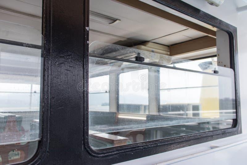 Finestra del metallo con le riflessioni da una barca immagini stock