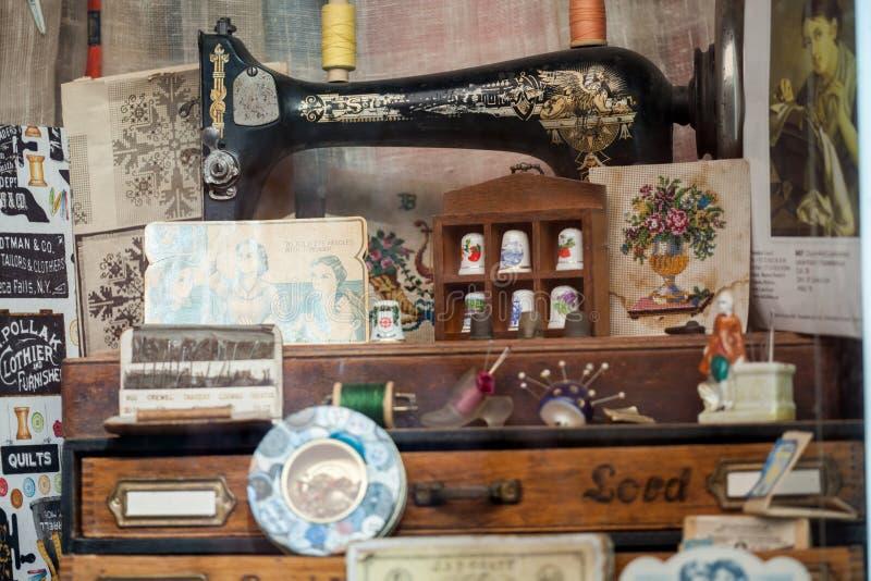 Finestra del negozio degli accessori di cucito Vecchia macchina per cucire fotografia stock