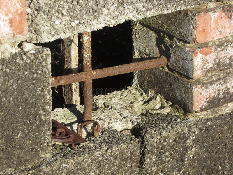 Finestra del seminterrato con le sbarre di ferro arrugginite sulla vecchia casa con mattoni a vista abbandonata immagini stock libere da diritti