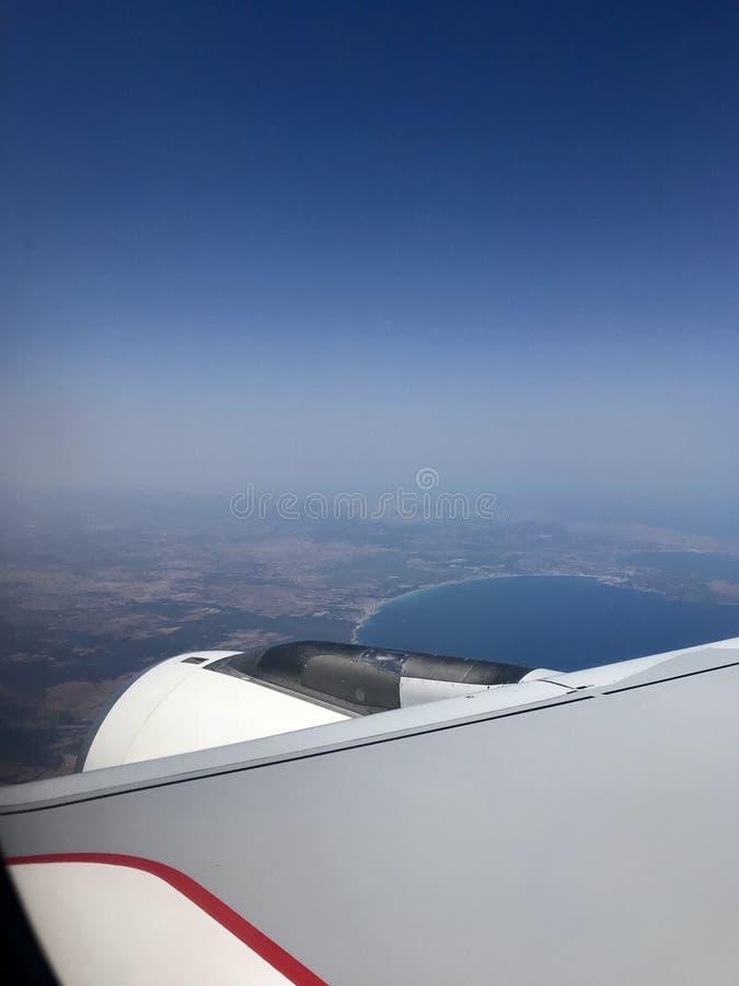 Finestra dell'aeroplano con il cielo della radura di Wing And dietro immagini stock libere da diritti