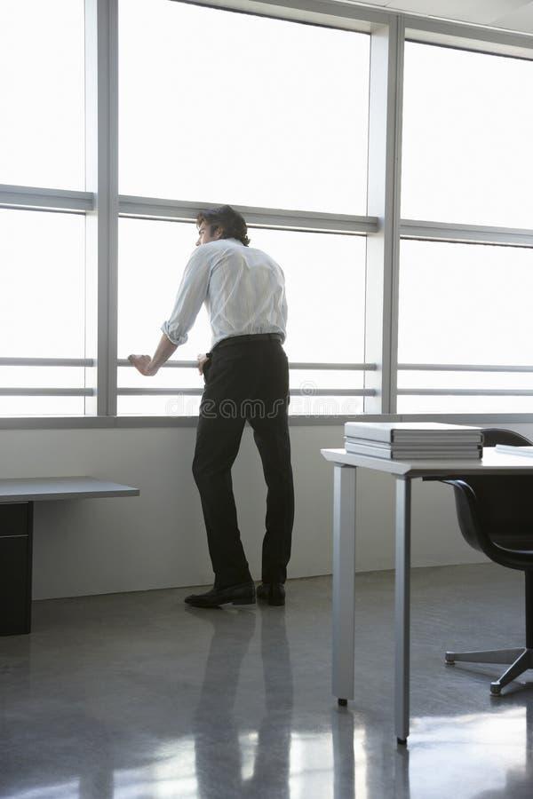 Finestra dell'ufficio di Looking Out Of dell'uomo d'affari immagini stock libere da diritti