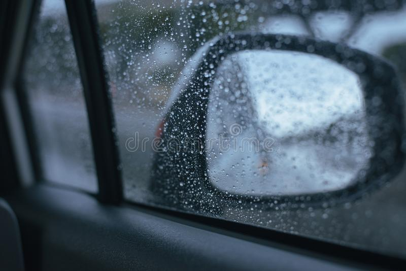 Finestra di automobile con le gocce di pioggia su vetro o sul parabrezza, traffico vago il giorno piovoso immagine stock