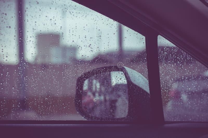 Finestra di automobile con le gocce di pioggia su vetro o sul parabrezza, traffico vago il giorno piovoso nella città fotografie stock libere da diritti