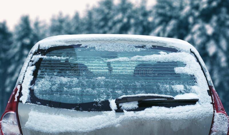 Finestra di automobile posteriore congelata inverno, vetro di congelamento del ghiaccio di struttura con neve sopra nevoso fotografie stock