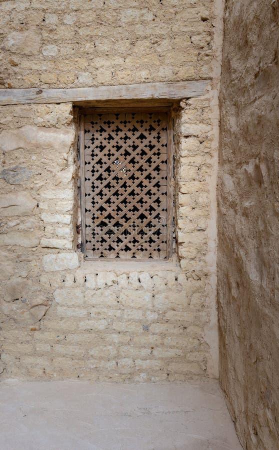 Finestra di legno antica con il modello geometrico basato sull'incrocio cristiano sulla parete di pietra del mattone esterno immagini stock libere da diritti