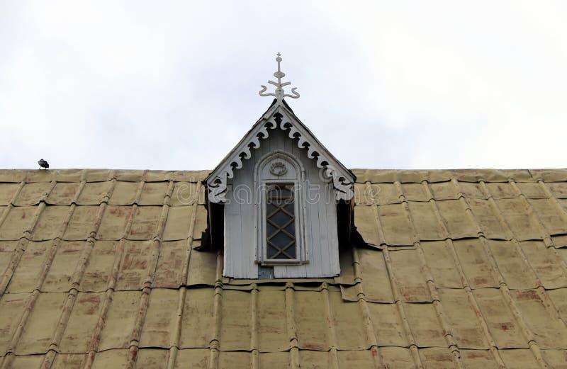 Finestra di legno della soffitta sul tetto con il fondo del cielo fotografie stock
