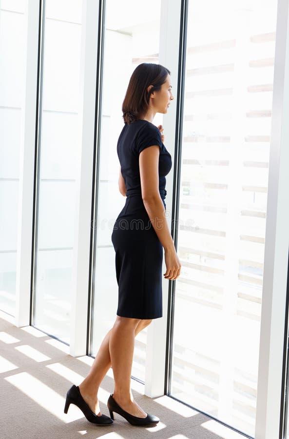 Finestra di Looking Out Of della donna di affari immagine stock
