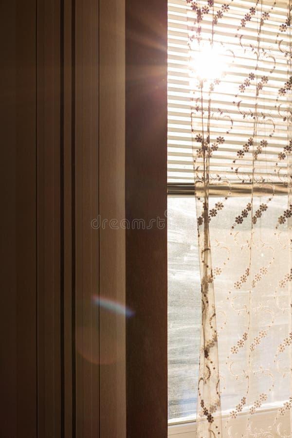 Finestra di plastica con i ciechi e tende con i raggi del sole fotografie stock