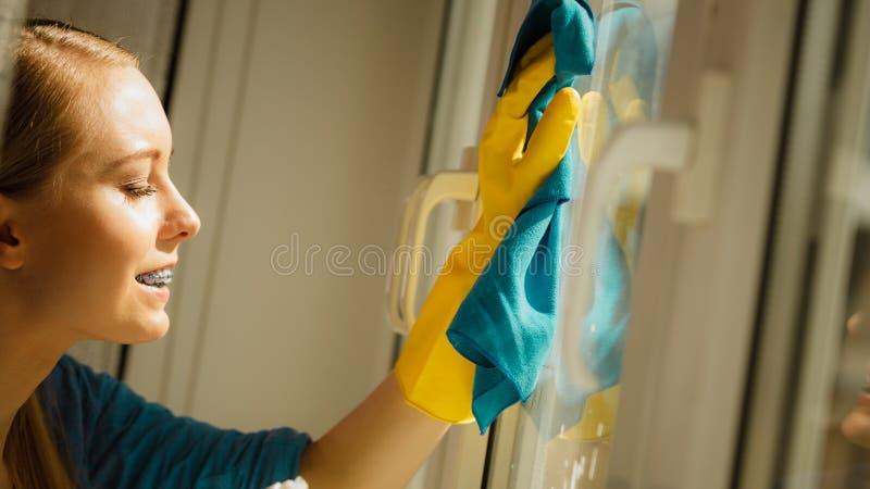 Finestra di pulizia della ragazza a casa facendo uso dello straccio detergente immagine stock libera da diritti