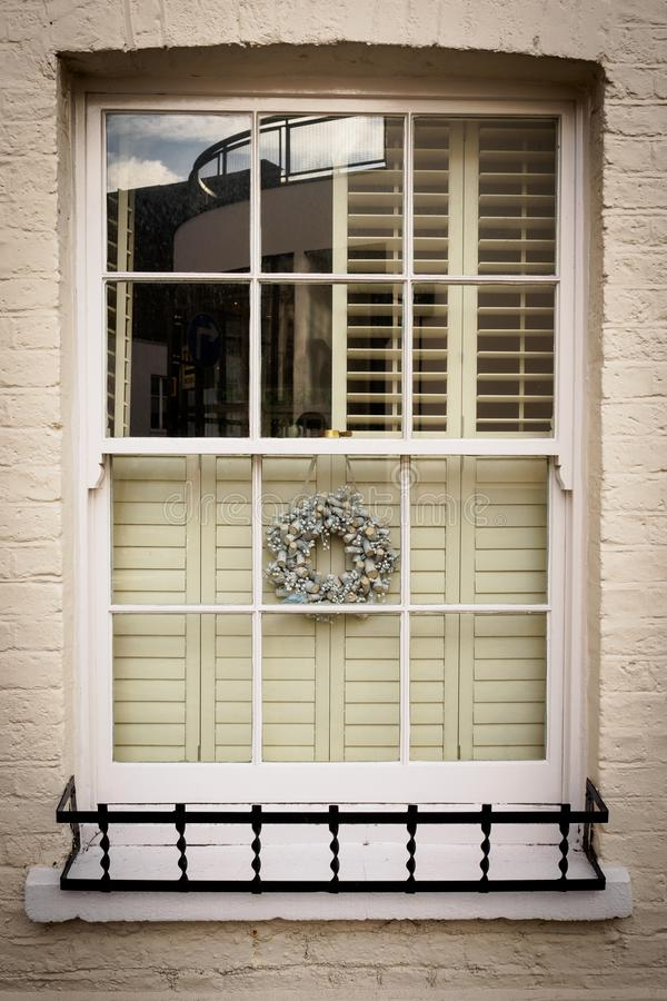 Finestra di Sash decorata con una ghirlanda d'argento di Natale a Londra Regno Unito fotografia stock