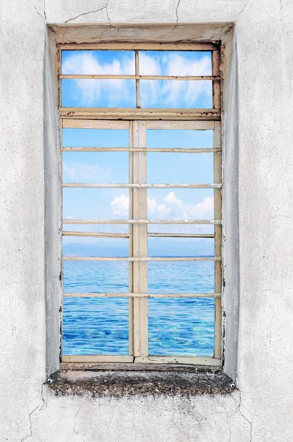 Finestra di vecchia casa del cemento con la vista del mare immagine stock libera da diritti