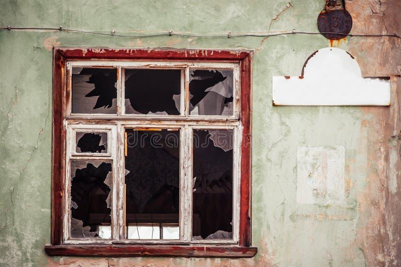 Finestra di vetro fracassata con la vecchia struttura di legno fotografie stock
