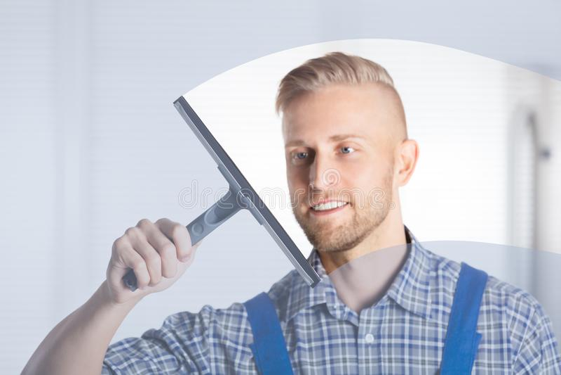 Finestra di vetro di pulizia del lavoratore con il seccatoio immagine stock