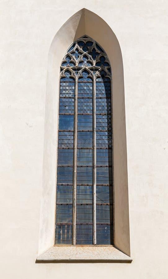 Finestra gotica alta sulla parete della chiesa fotografia stock