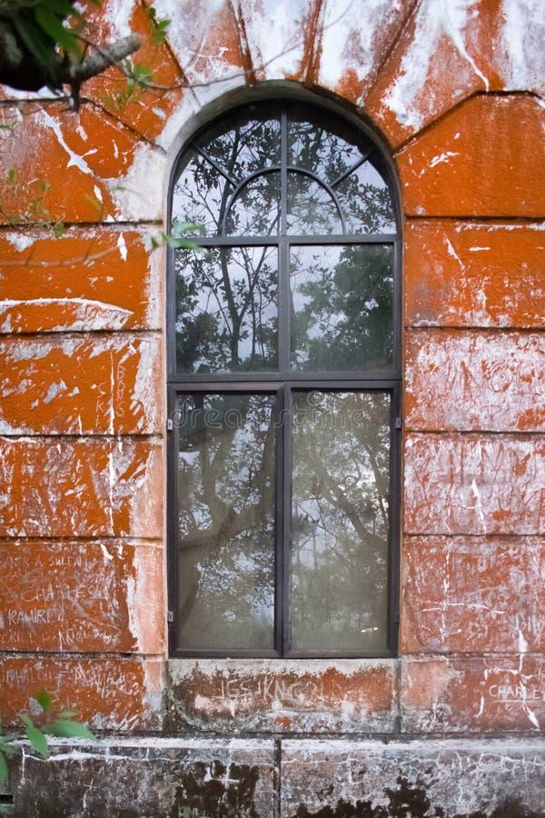 Finestra isolata con un mattone rosso rustico muscoso fotografie stock