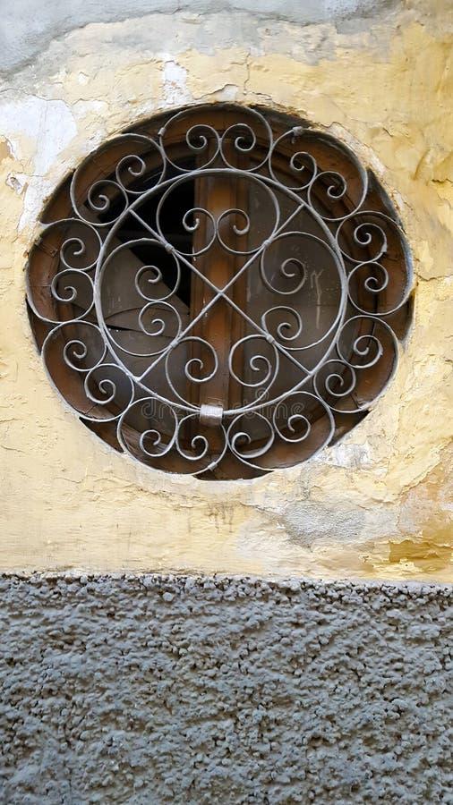 Finestra rotonda in parete di pietra con la griglia del metallo fotografie stock libere da diritti