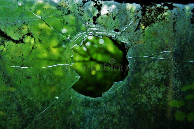 Finestra rotta con le crepe attraverso vetro che esamina gli alberi immagini stock libere da diritti