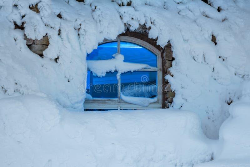 Finestra scura in una notte fredda e nevosa di inverno fotografia stock