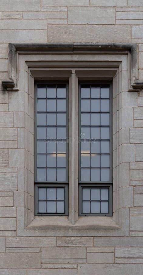 Finestra sottile alta sulla vecchia costruzione di mattone del cemento immagine stock