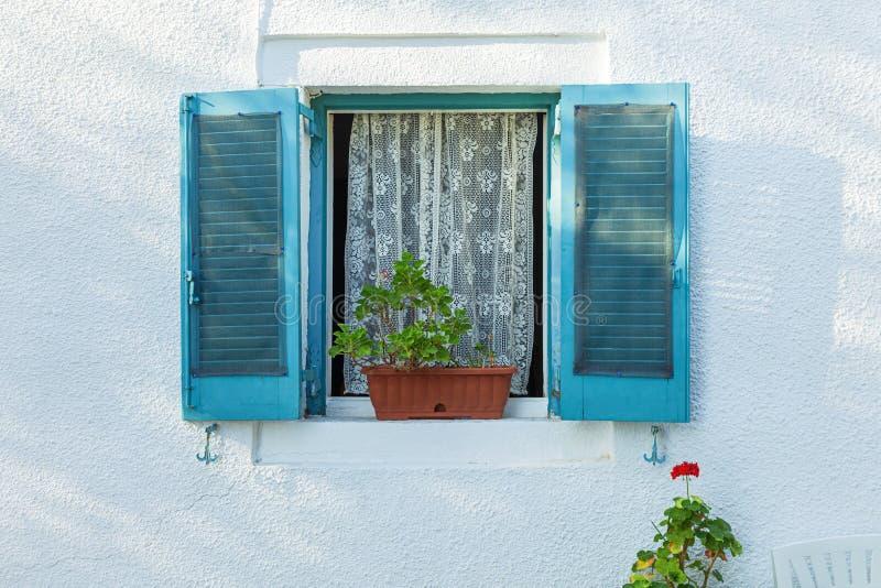 Finestra tipica con gli otturatori blu sulla parete bianca fotografia stock libera da diritti
