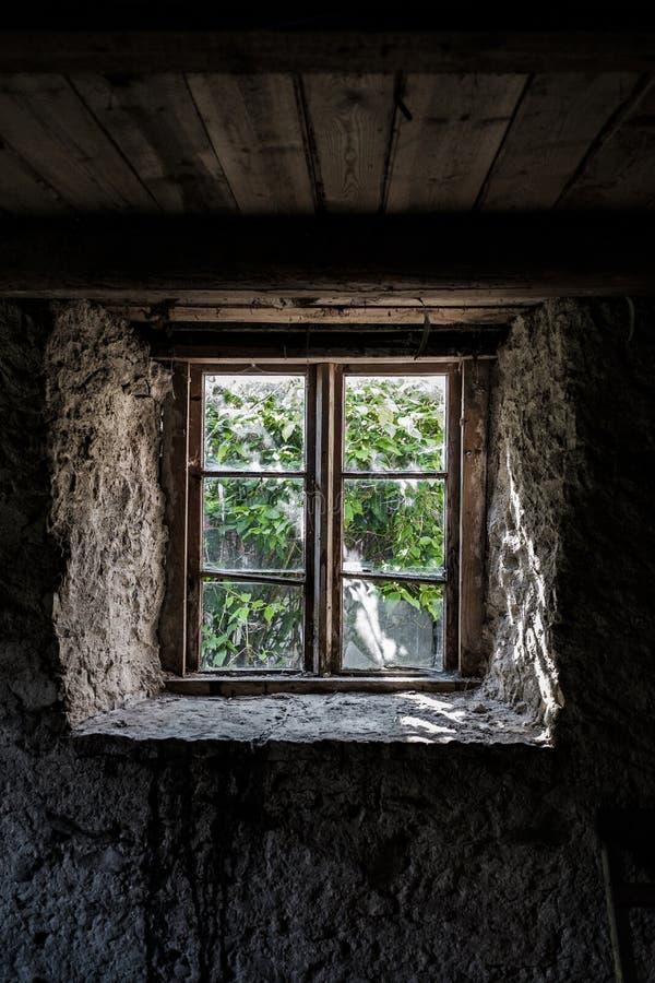 Finestra in una vecchia casa di pietra con una vista del giardino immagine stock