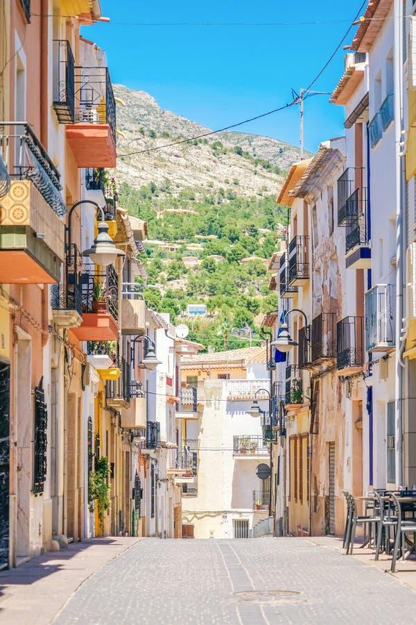 Finestrat, Hiszpania - 12 2019 Czerwiec: Wąska ulica w Finestrat starym miasteczku z pięknymi domami i halnym tłem obraz royalty free