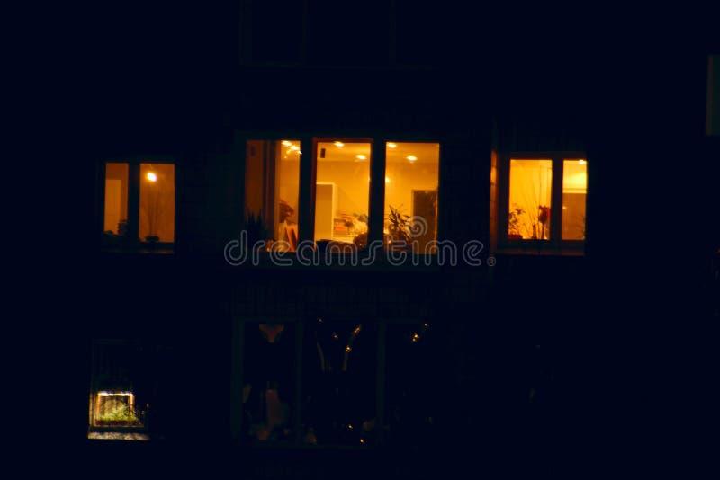 Finestre accese di notte delle case immagini stock