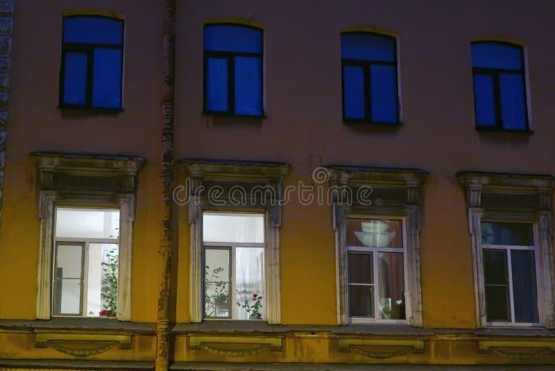 Finestre accese di un edificio residenziale di vecchia notte fotografie stock libere da diritti